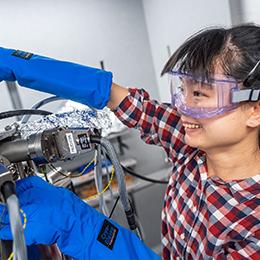 Researcher with liquid helium tank